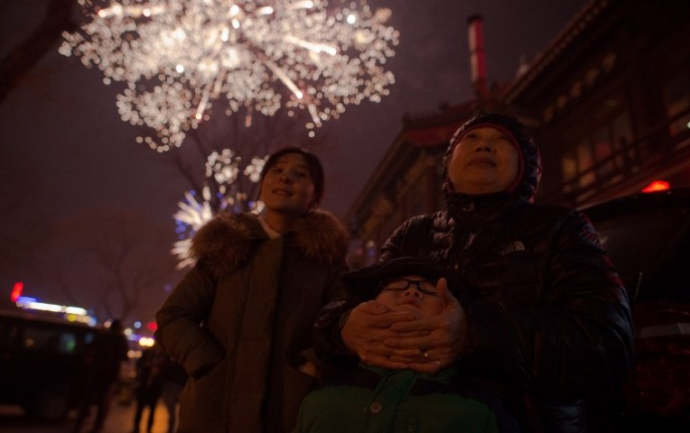 La gente mira los fuegos artificiales en una calle en Pekín el 27 de febrero de 2017, la víspera del Año Nuevo Lunar.